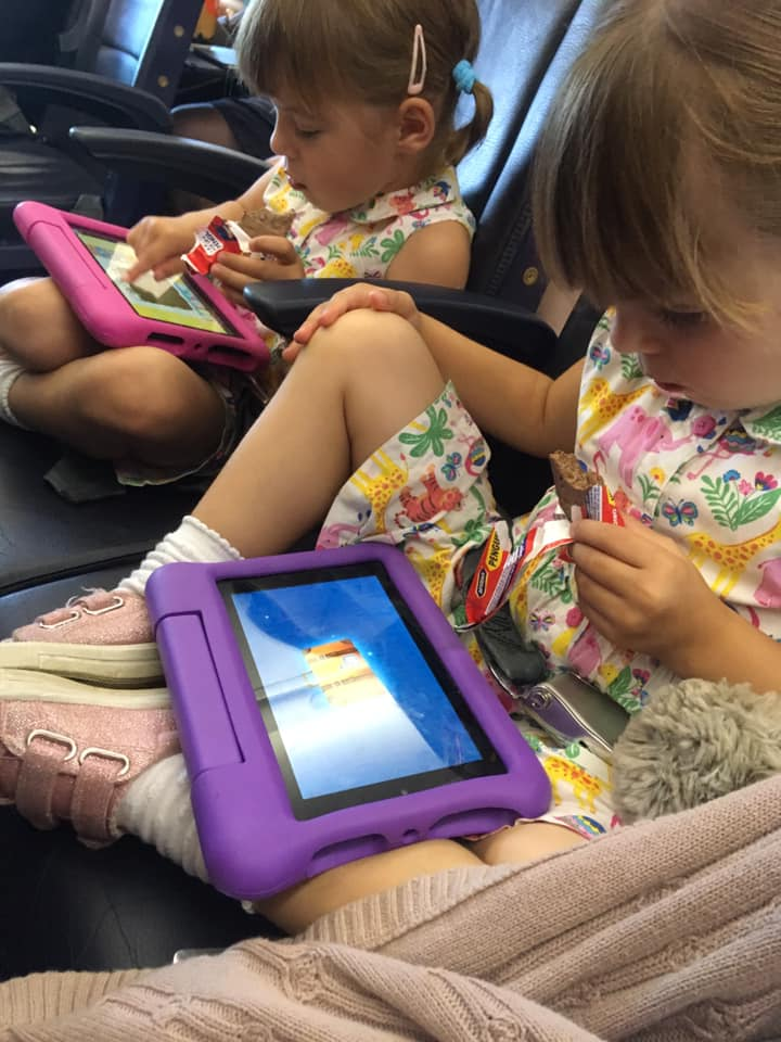 two children playing on their kindles on the airplane