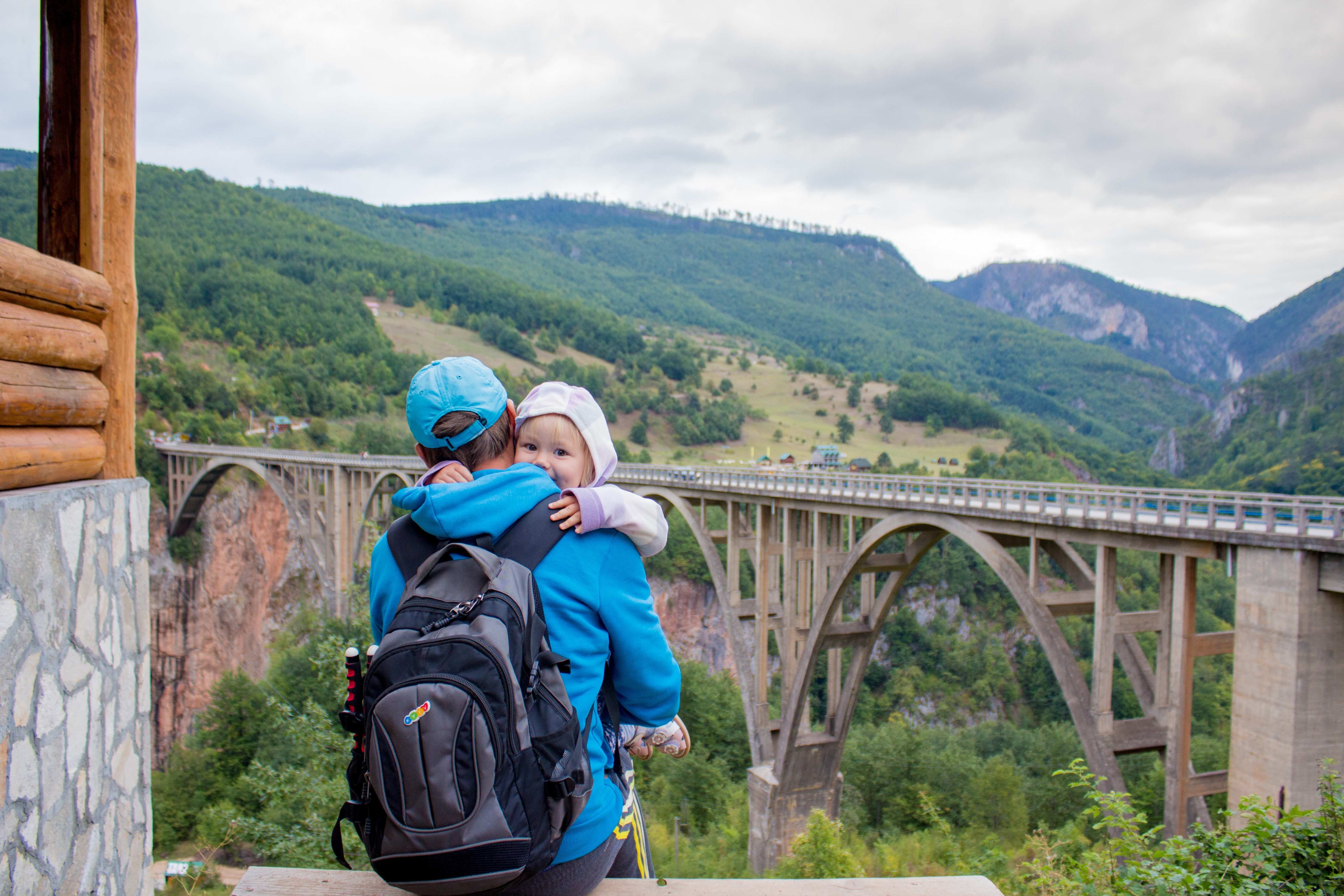 dad carrying child, looking at a bridge and his carry on bag
