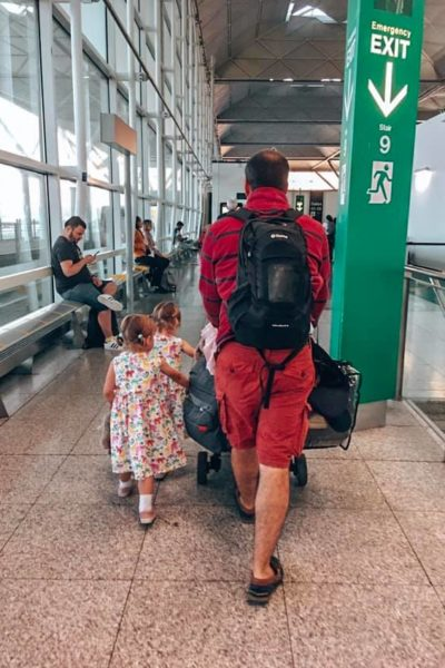 Dad walking in the airport with his children and a backpack on