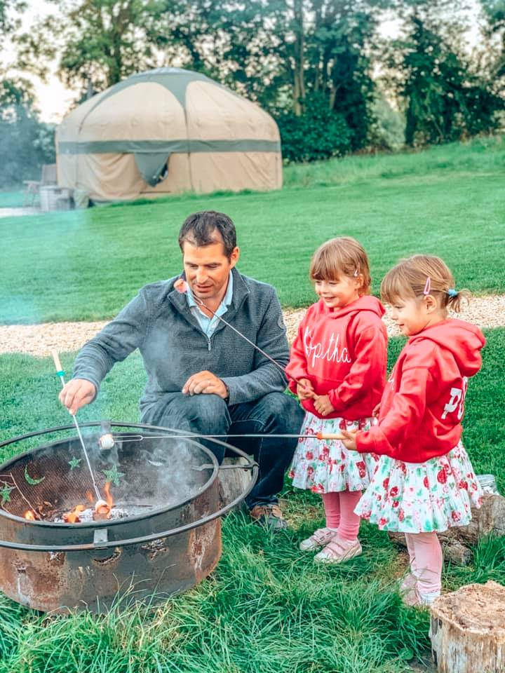 daddy and children round the campfire toasting Marshmallows