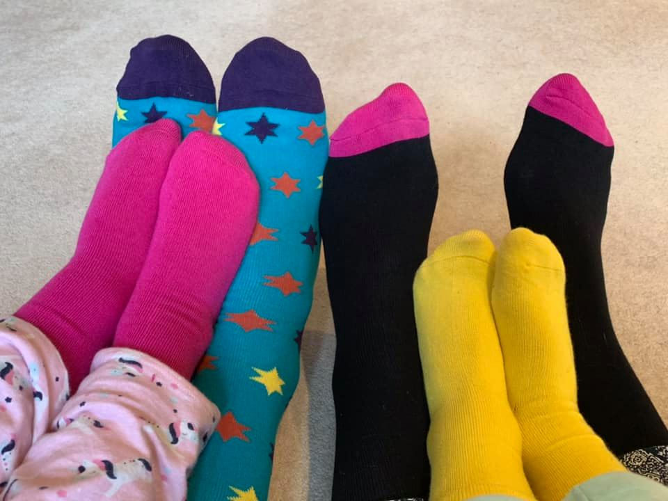 4 pairs of feet with socks on