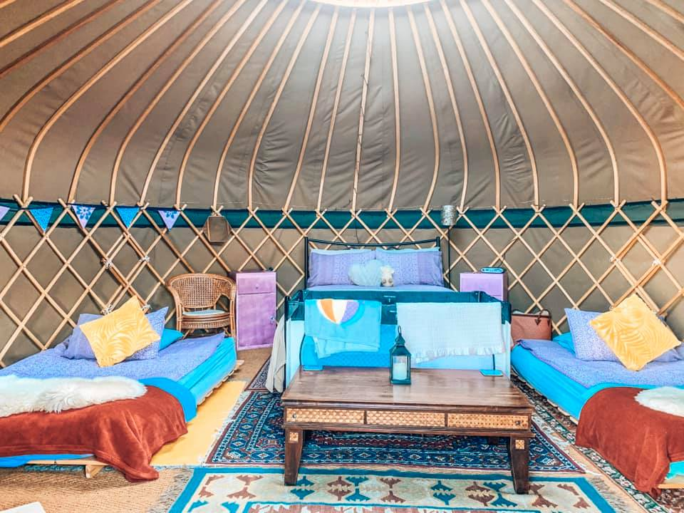 Inside of a yurt with a double bed, two singles and a cot