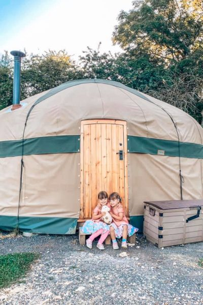 Twins sitting on the doorstep of the yurt