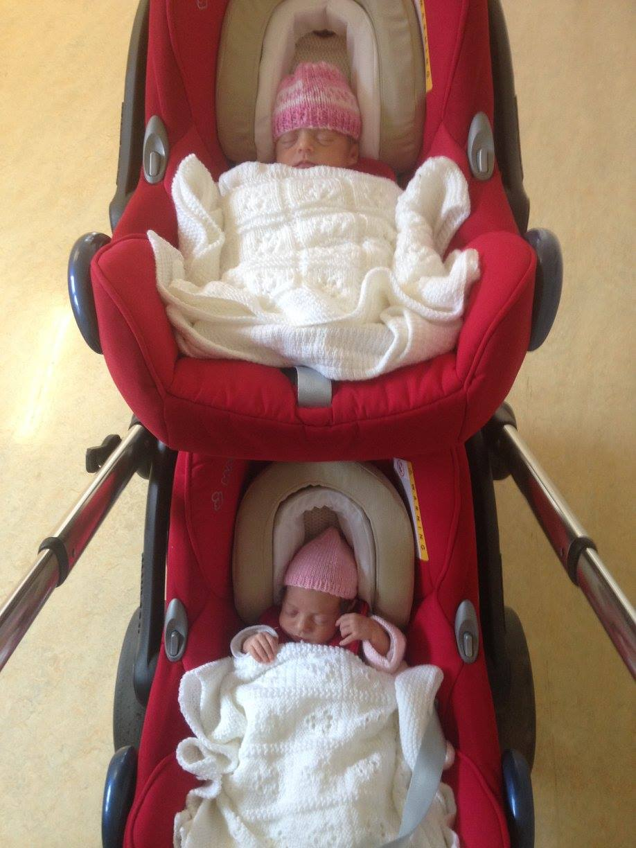 twins sitting in their car seats at the front door