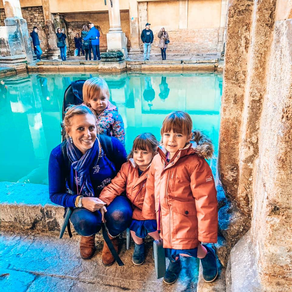 A family sitting in front of the Roman Baths in Bath.