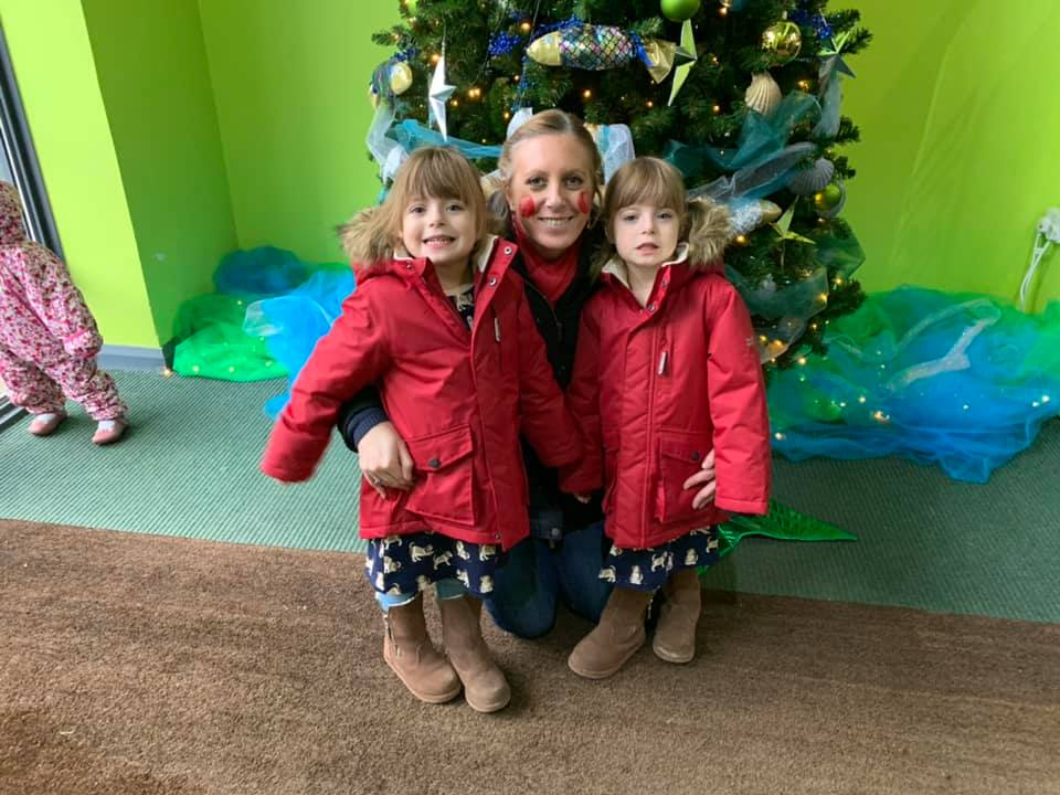 Twins and mummy in front of the Christmas tree at Bluestone