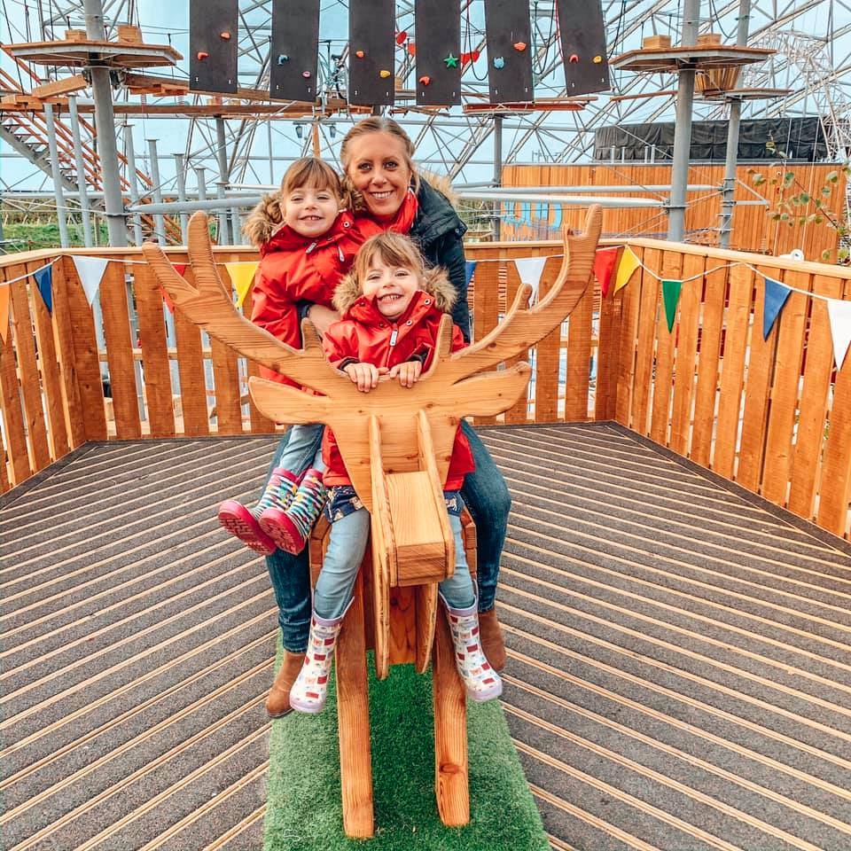 Riding a wooden reindeer inside the Serendome at Bluestone Wales