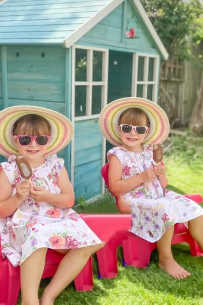 two girls sitting outside a little beach hut style wooden playhouse on the grass. The girls have sun hats on with summer dresses. The wooden playhouse is a green colour