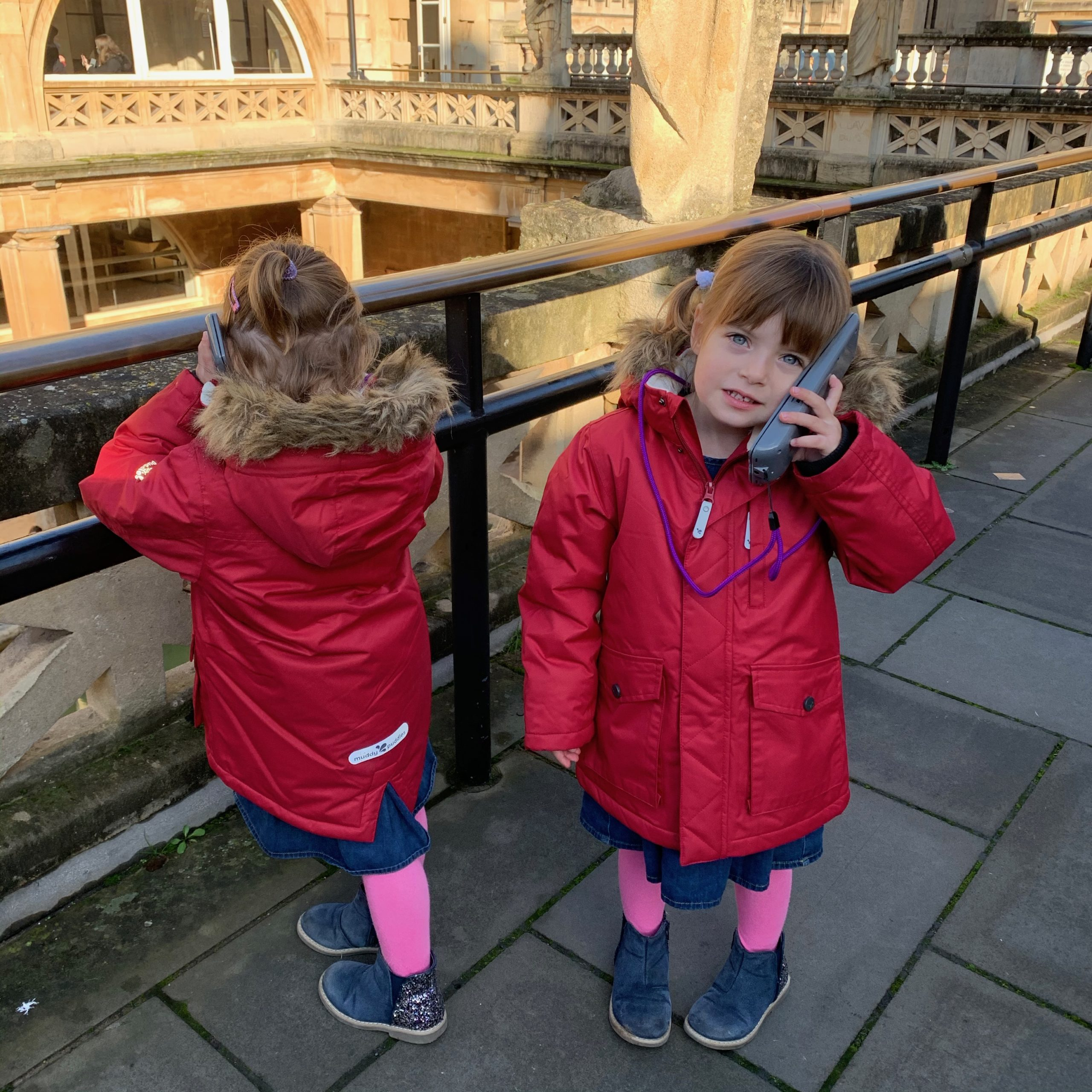 Twins listening to the audio system at the roman baths. A great day out if in Bath with kids