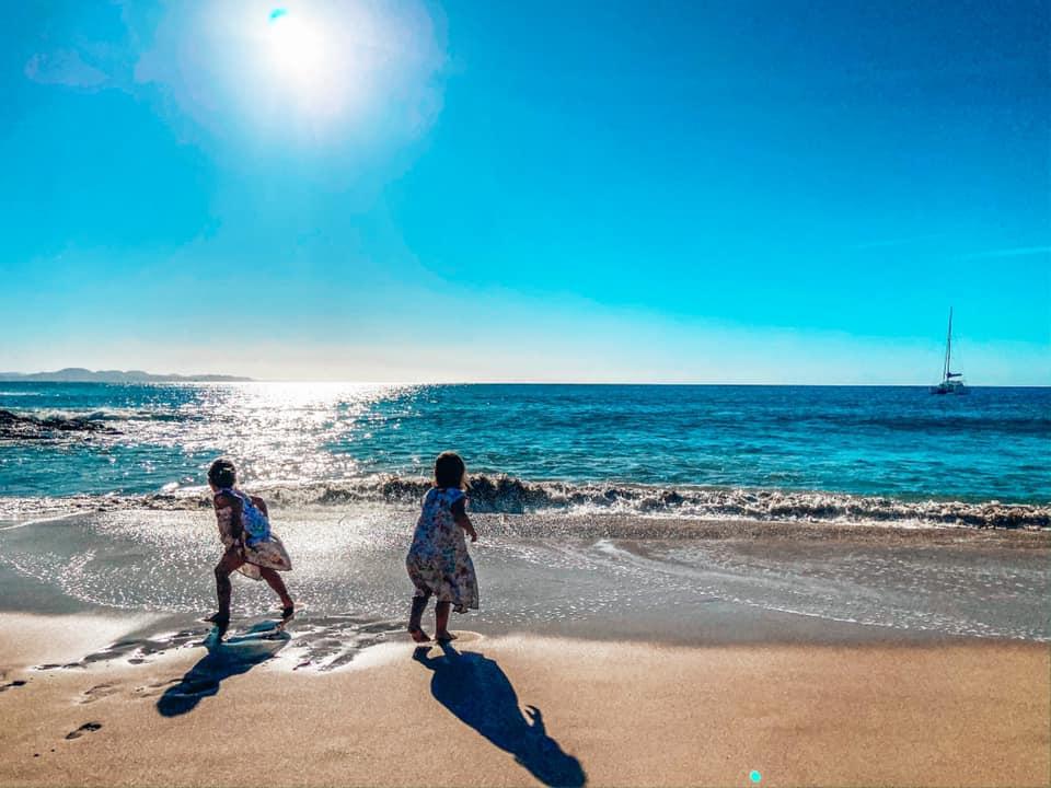 Twin girls running on the beach at Papogayo beach