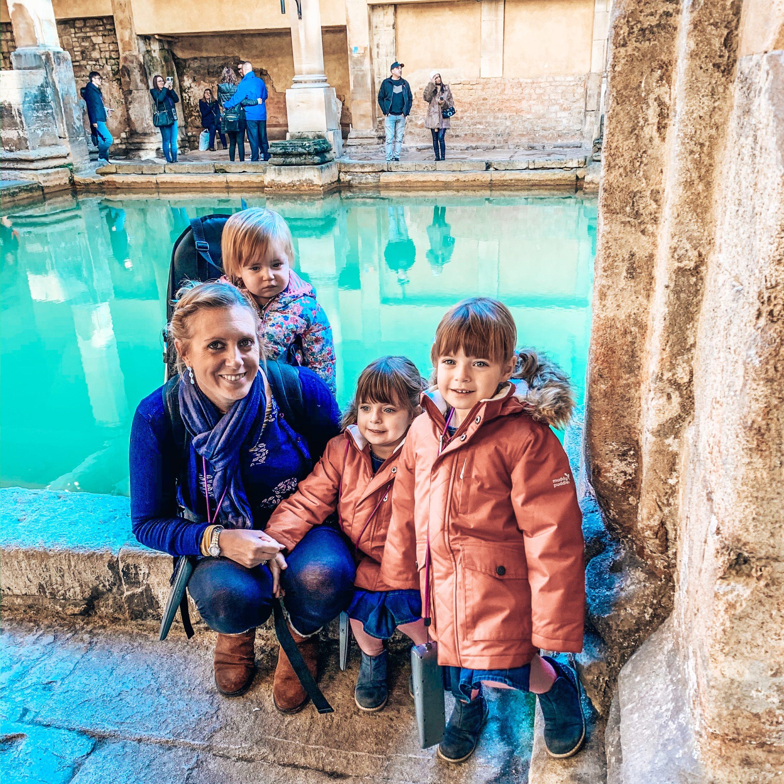 Twins and mum smiling in front of the roman baths. A great day out if in Bath with kids