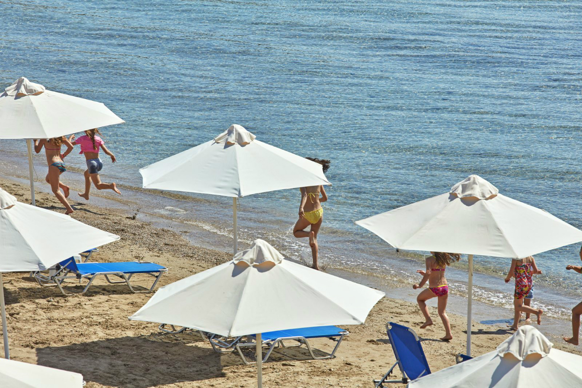 picture of the beach from the hotel looking down to people in swimwear, white sun brollies and blue sun chairs