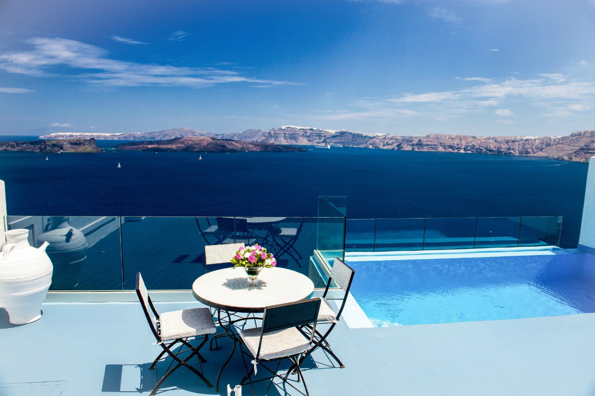 infinity pool in Santorini on a private terrace, table and flower display