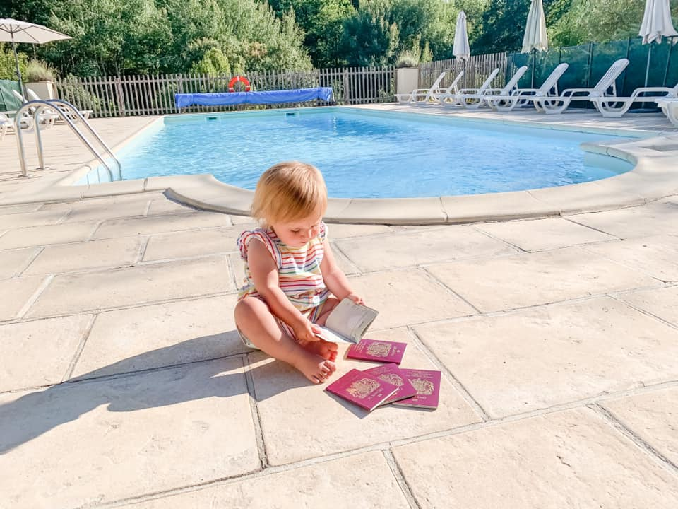 baby sat on patio alongside a swimming pool in striped top looking in a passport surrounded by four more closed British passports