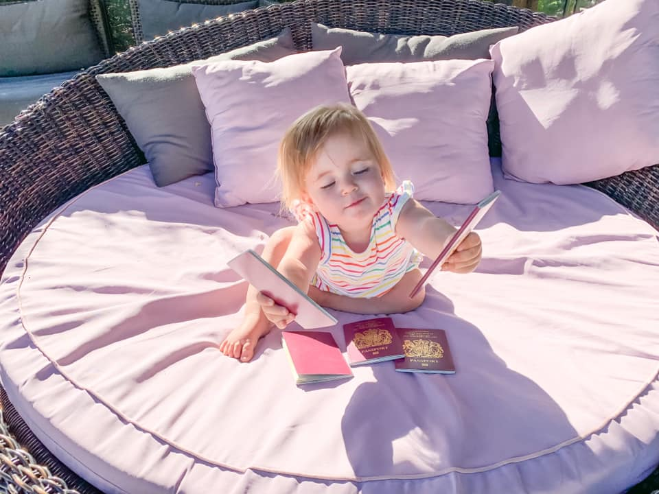 baby in striped top holding passport on a big round pink sun chair surrounded by pin and grey cushions