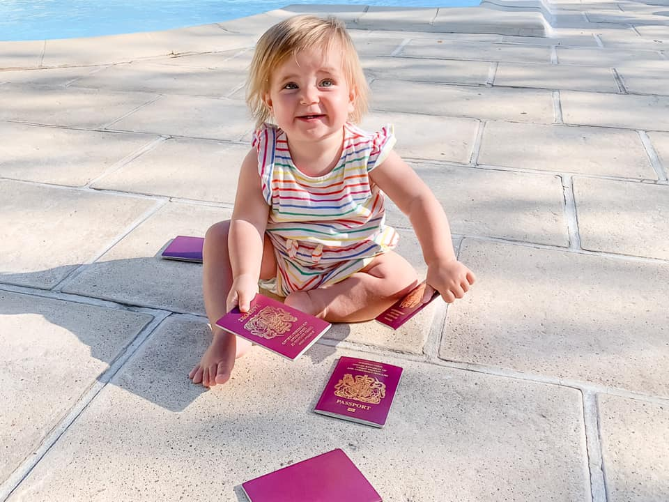 baby in striped top sat on the floor beside a pool outside holding multiple passports