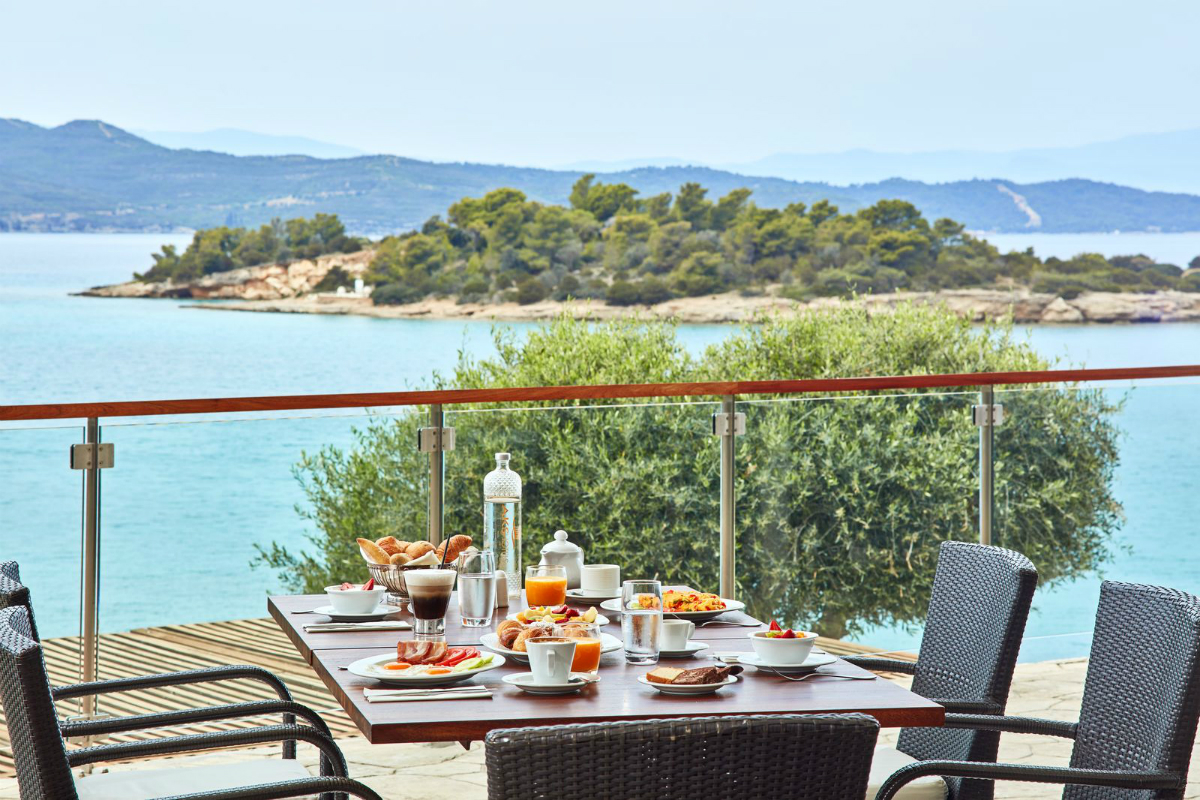 picture of breakfast set on a table alongside a glass balcony overlooking a tree and blue sea