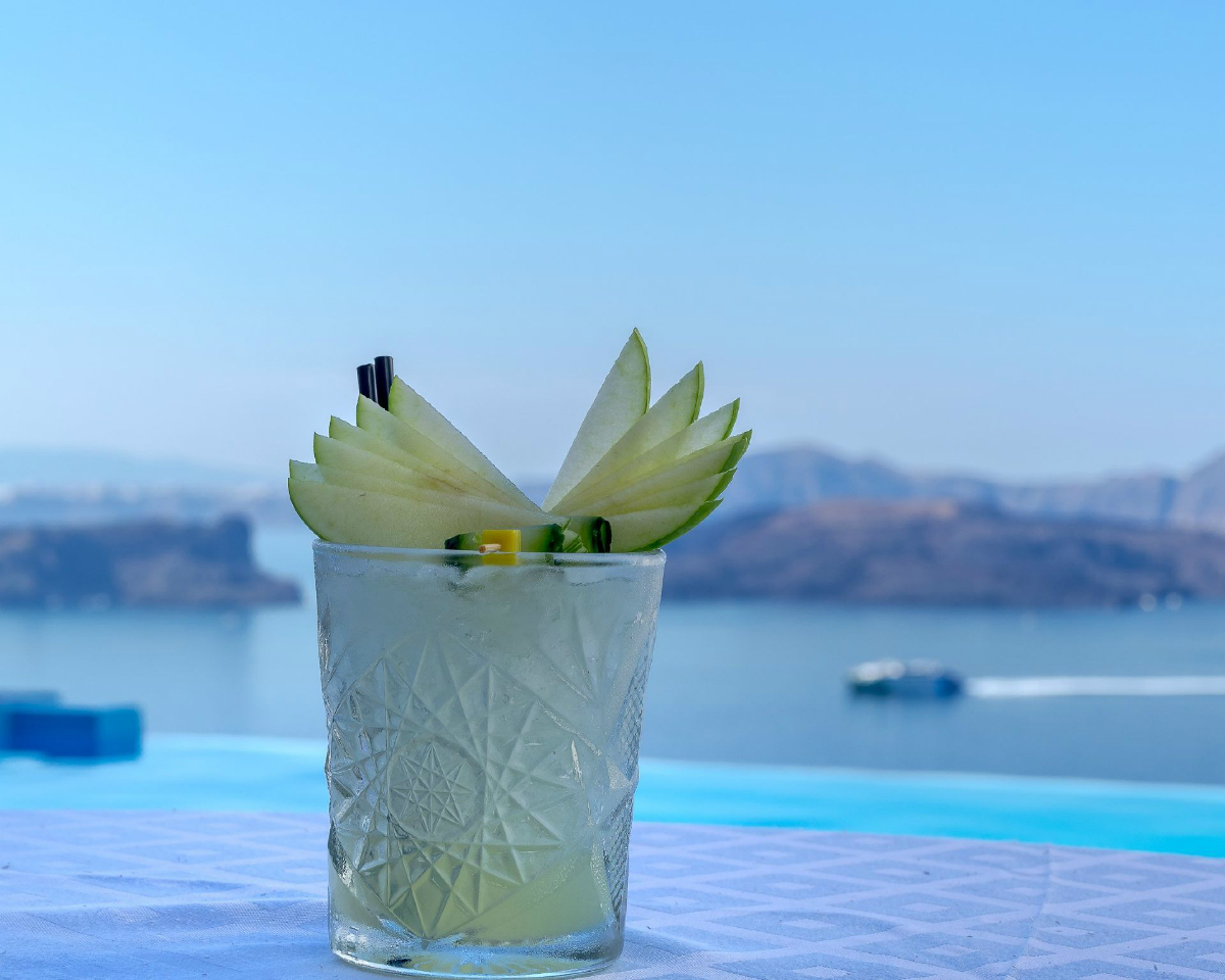 picture of a cocktail (which and yellow) with flower or fruit on a table with a blurred background of the sea and a boat sailing across the ocean