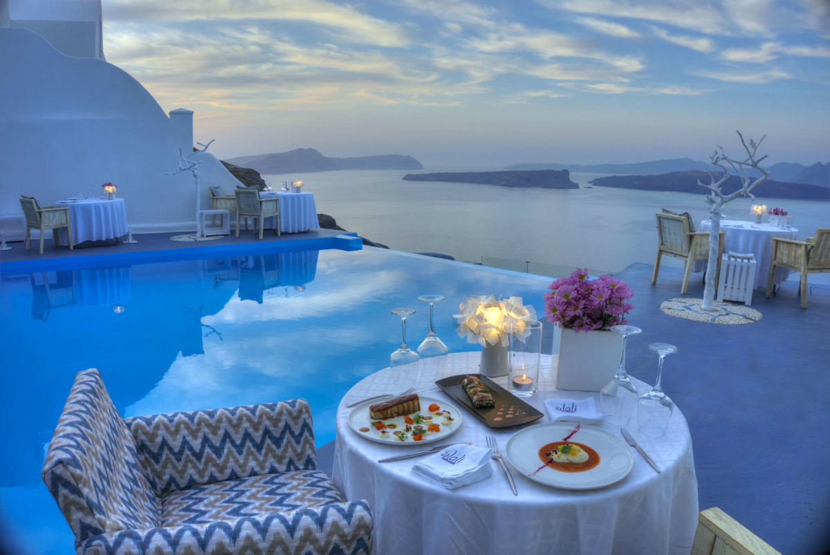 restaurant table set alongside a pool, with food, flowers and sea