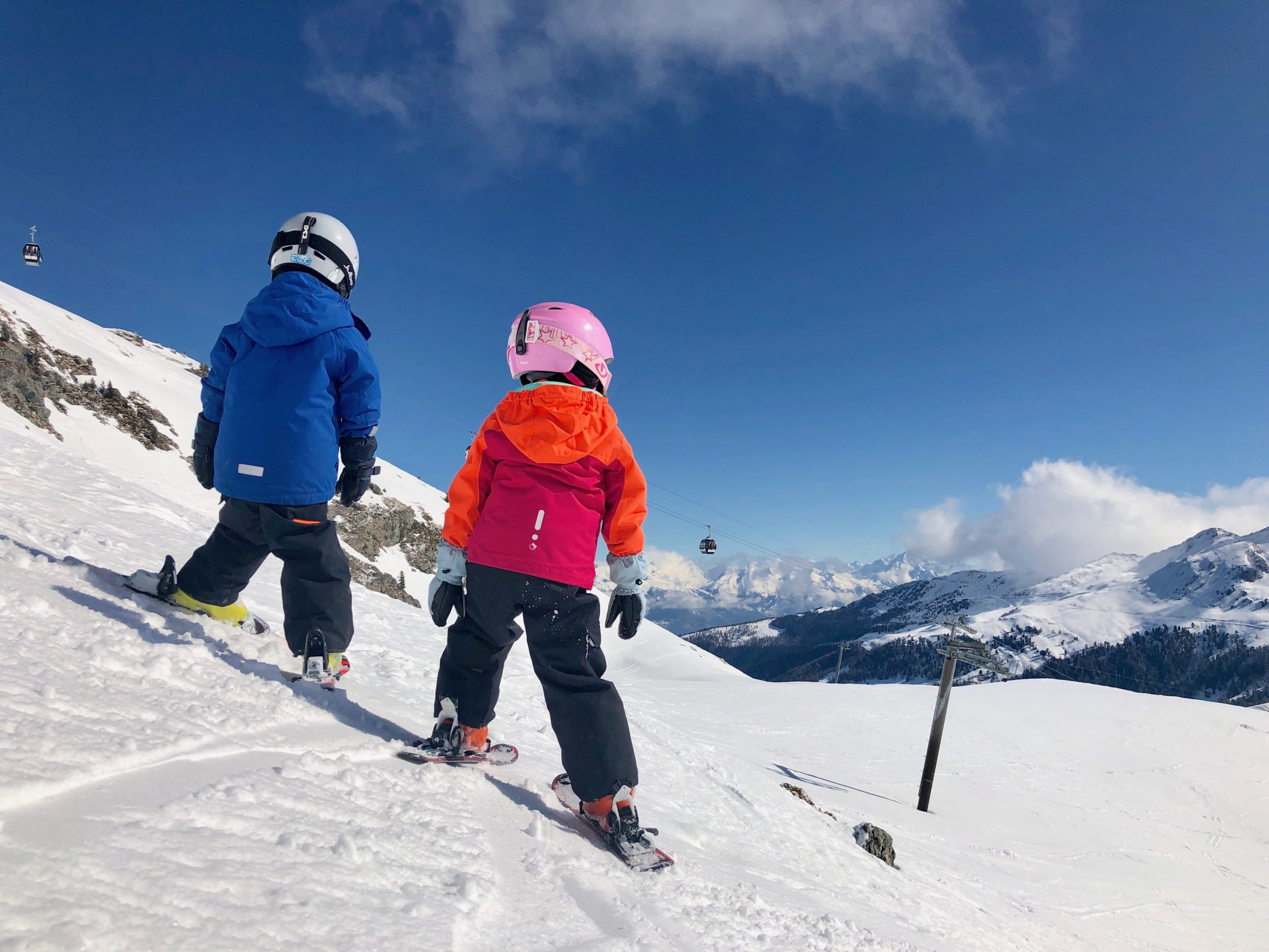 picture of boy and girl facing away from the camera towards the slopes wearing skis, gloves, a red and blue jacket and pink and white helmet
