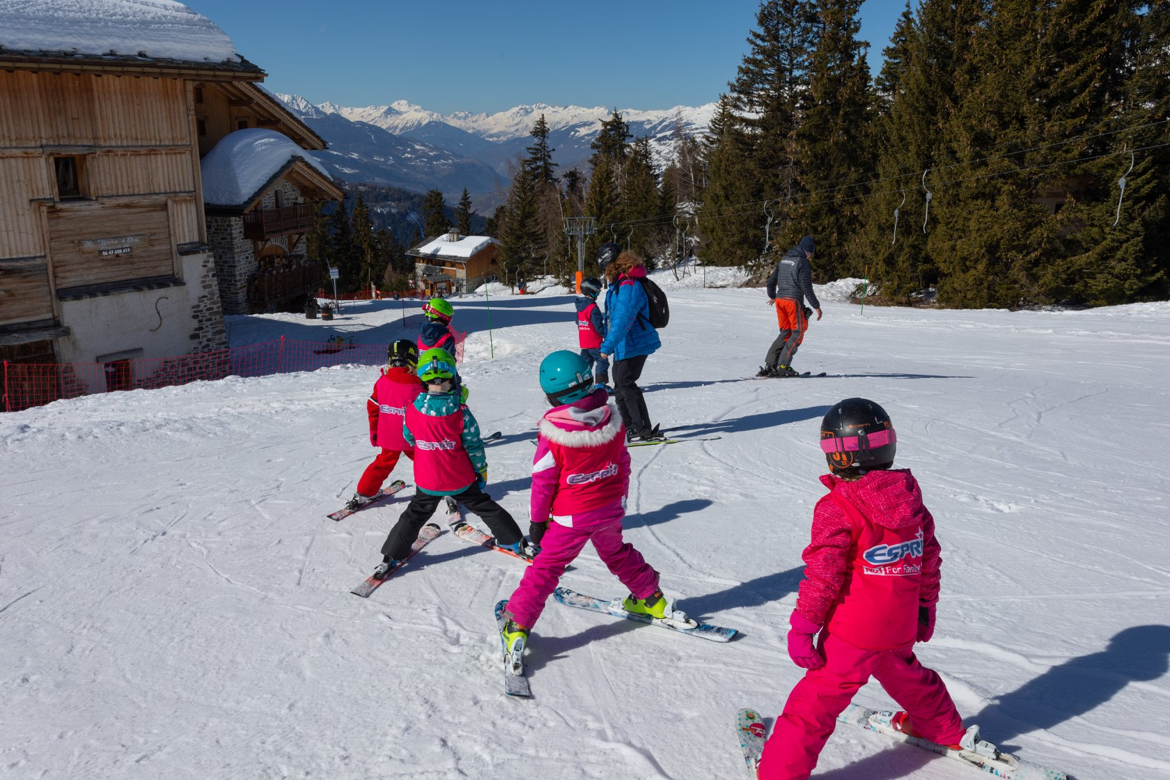 children on the snow at ski practice all wearing pink jackets and trousers with green, black and blue helmets listening to adults wearing blue jacket and backpack