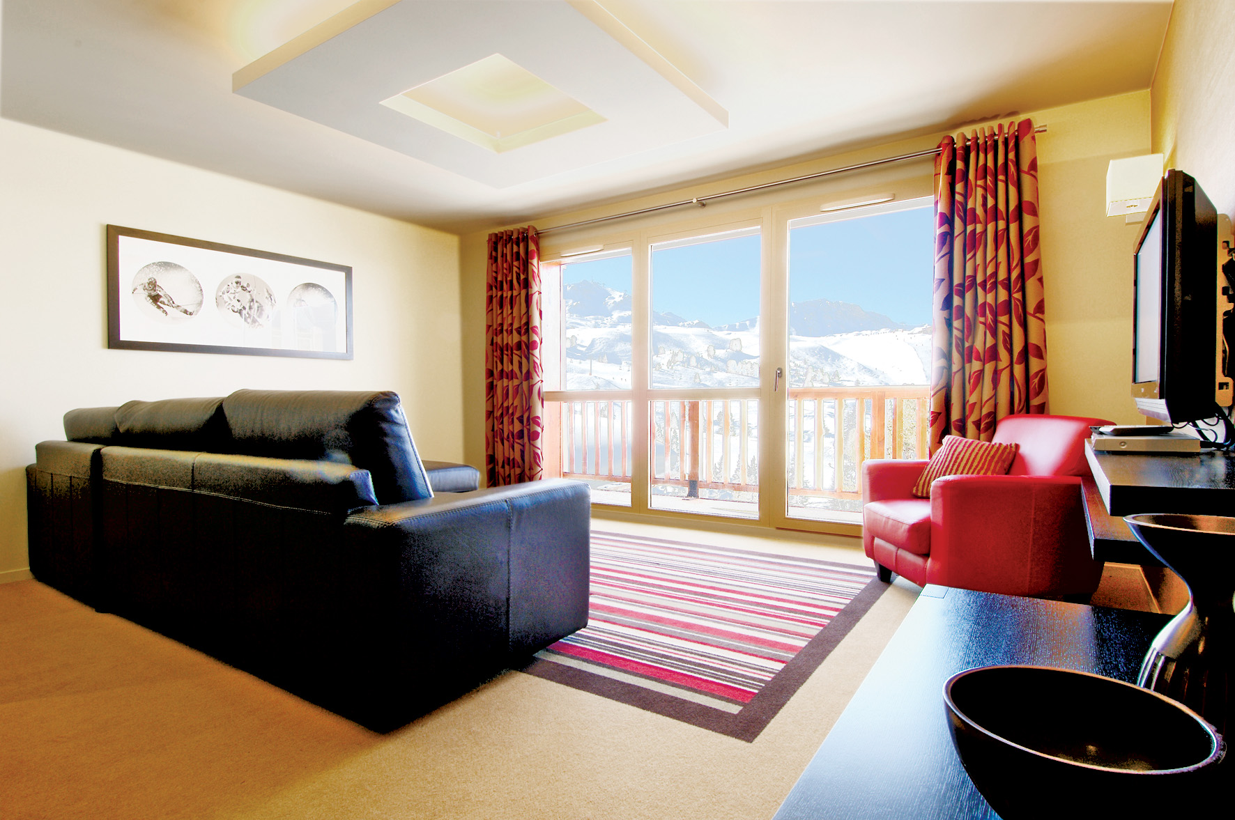 view of the lounge with red and beige curtains, leather sofa, red chair, striped rug facing towards floor to ceiling sliding door overlooking the ski slopes/mountains