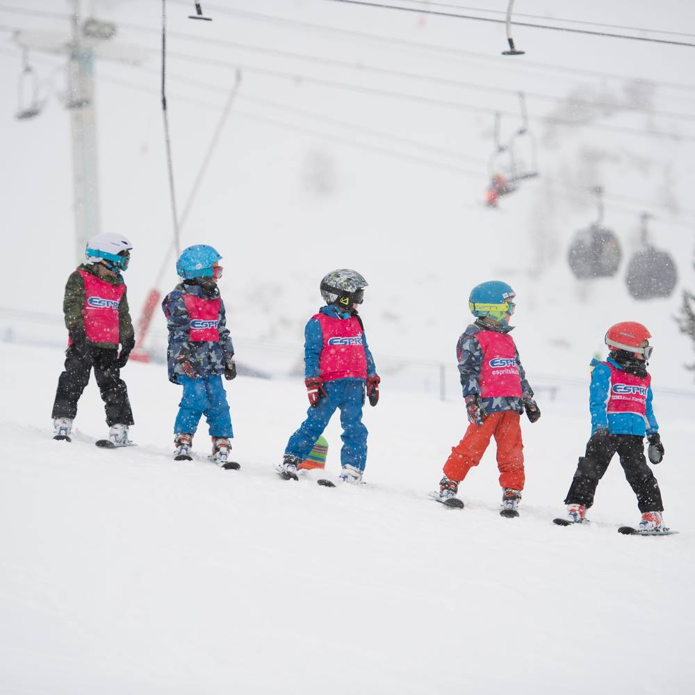 picture 5 children in camo, blue and orange ski trousers all wearing skis and a pink 'espirit' bib. Coloured helmets include blue, white, grey, blue and red all children looking to their left with the ski lift unfocused in the background