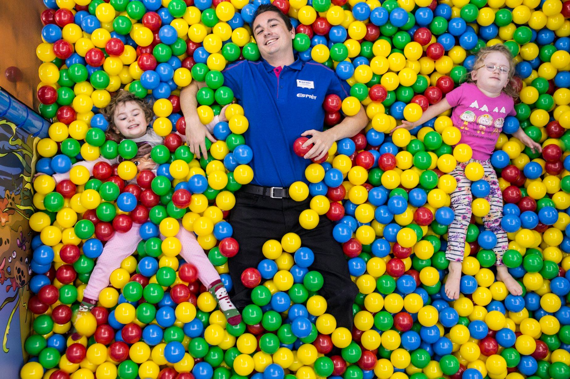 picture of esprit children's entertainer wearing a blue t-shirt and black trousers laid in a ball pool looking up to the camera along side two girls wearing pink also laid on their back in a multi coloured ball pit