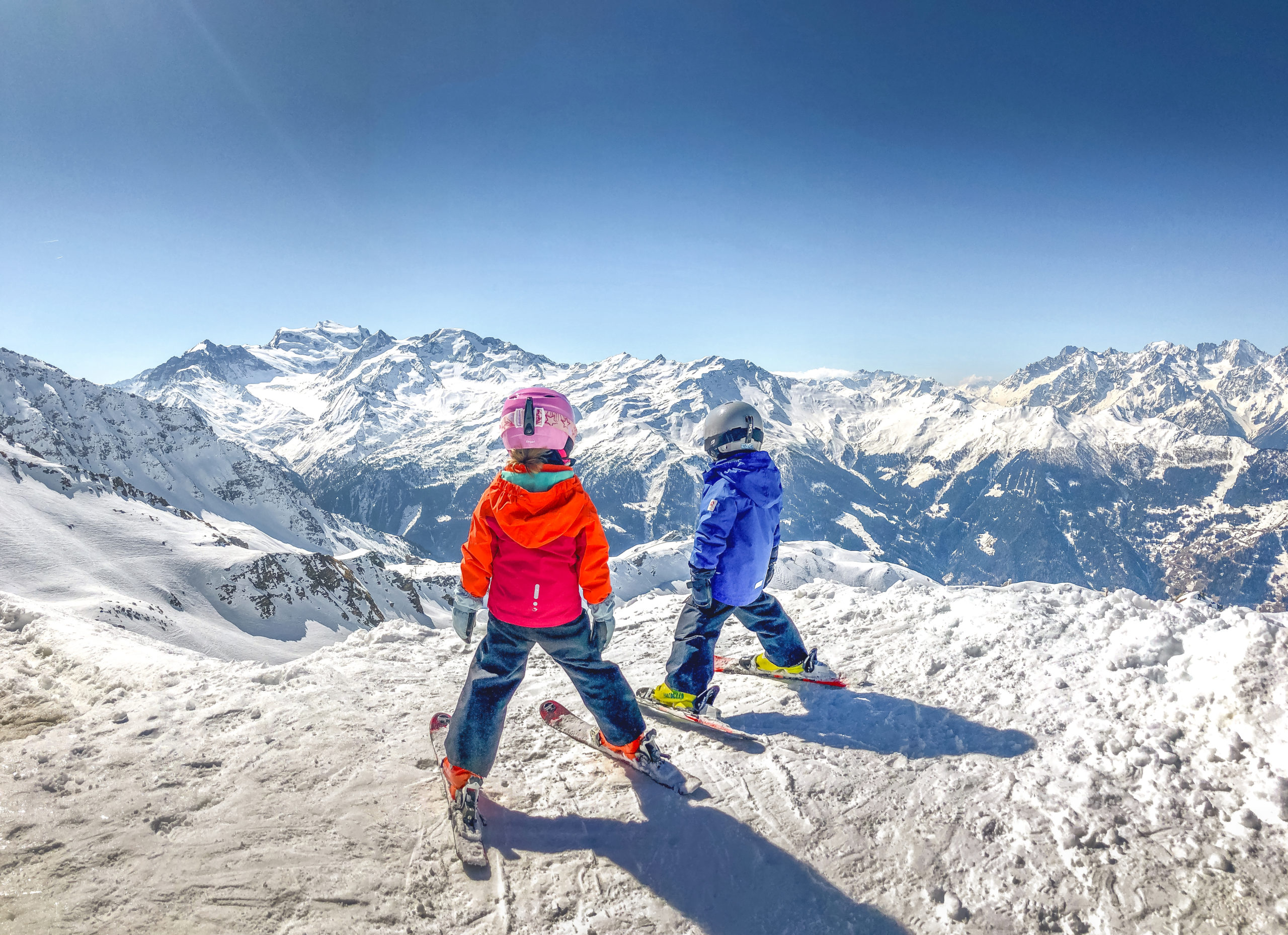 boy and girl on top of the mountain looking away from the camera wearing red and orange and blue jackets. Pink helmet, yellow and orange boots in skiis.
