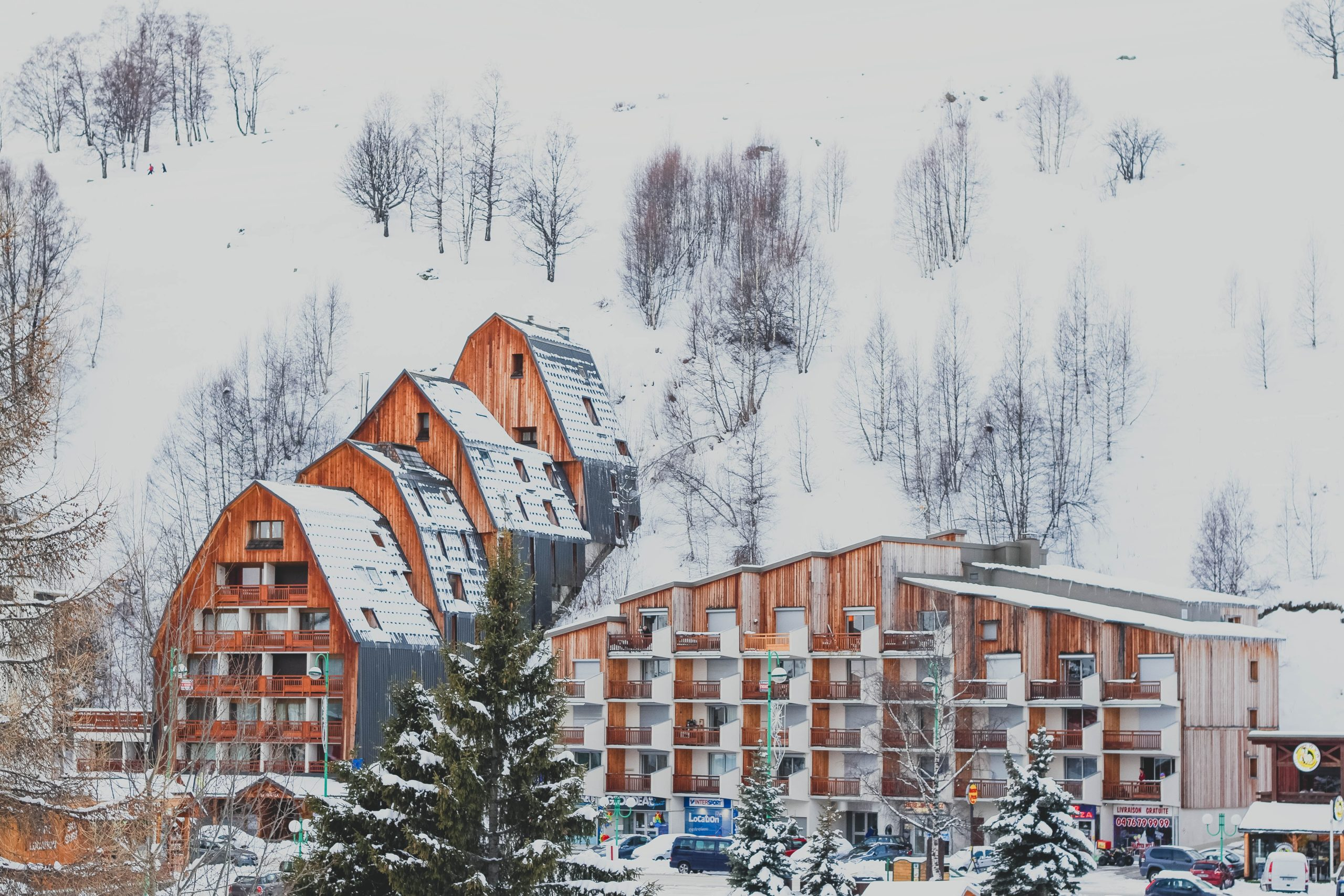 picture os snow covered multi story hotel built in the side of a mountain with balconies covered in wood