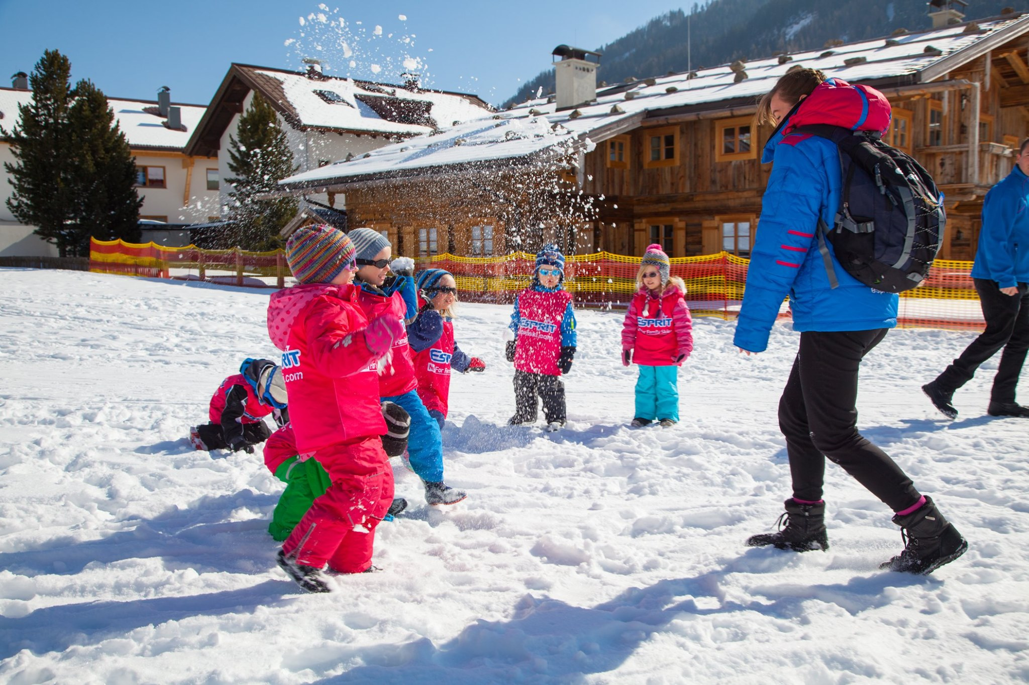 6 preschoolers dressed in pink overcoats, hats and sunglasses throwing snowballs in the snow towards an adult in a blue coat, black leggings and ski boots