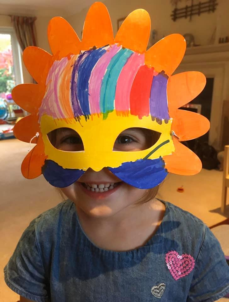 Child with colourful mask on that she has made