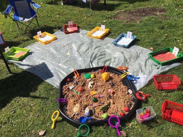 The sand pit with toys around the edge and some hidden in the sand