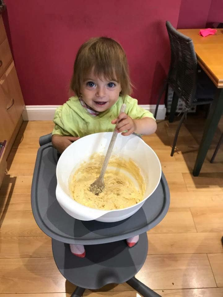Toddler sitting in her highchair with a mixing bowl making cakes