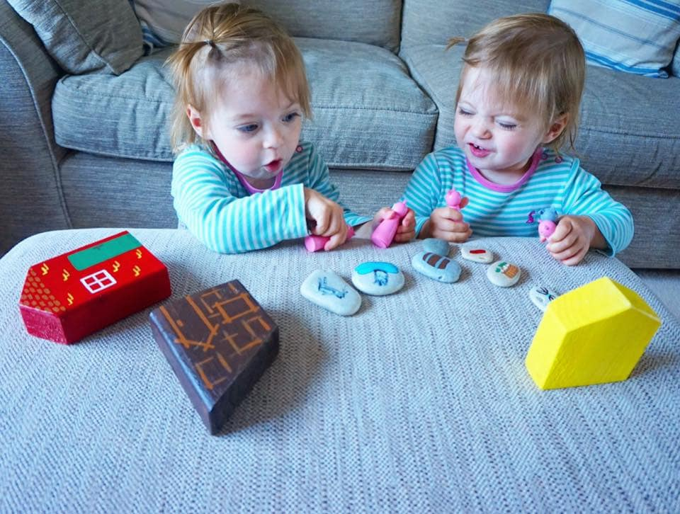 Toddlers acting out the three little pigs with houses and three little wooden pigs