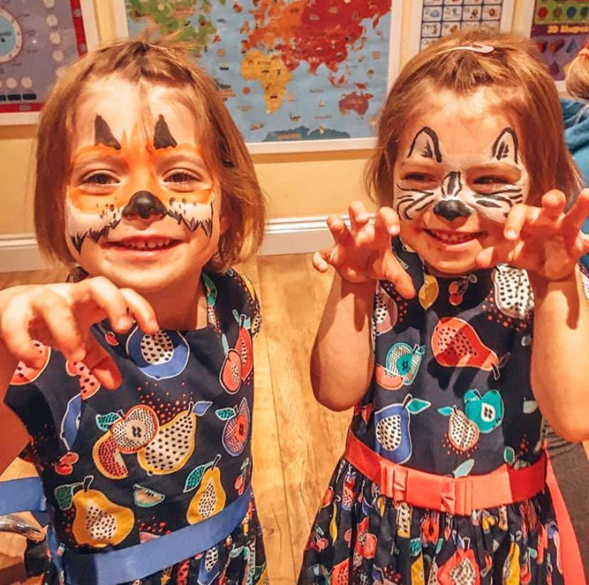 Twins with faceprint on. One as a zebra and the other as a tiger with their hands in the air.