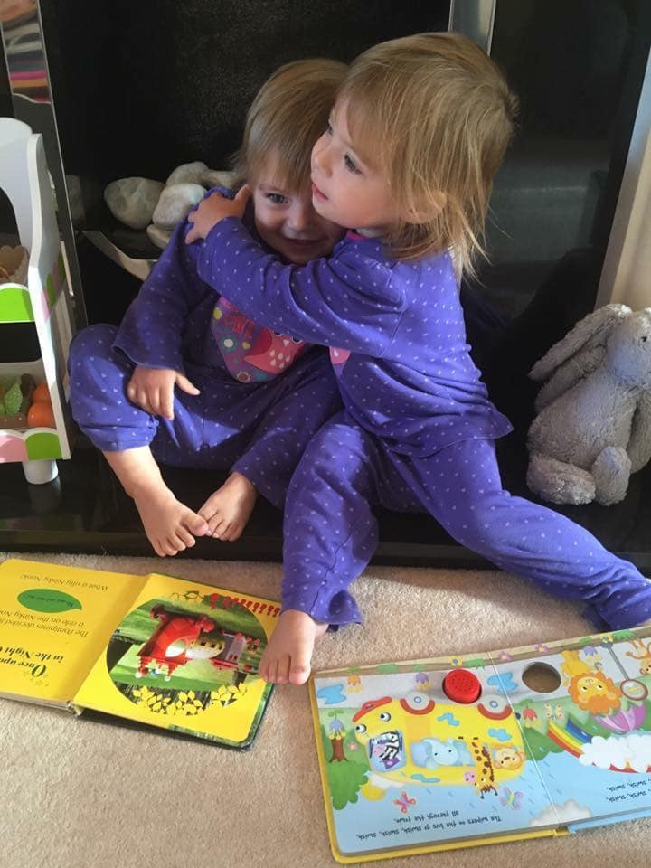 two toddlers sitting on the floor reading books together