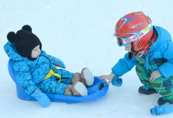 baby and toddler in the snow with the baby in a sledge being pulled by the toddler