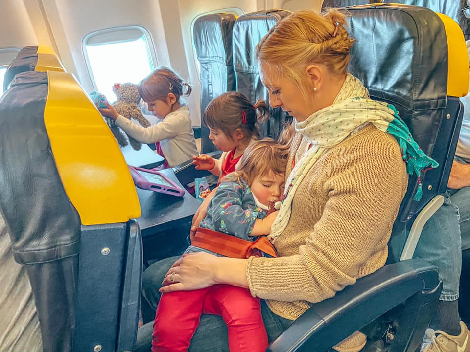 Baby asleep on mothers lap on board an airplane whilst two other children play on devices