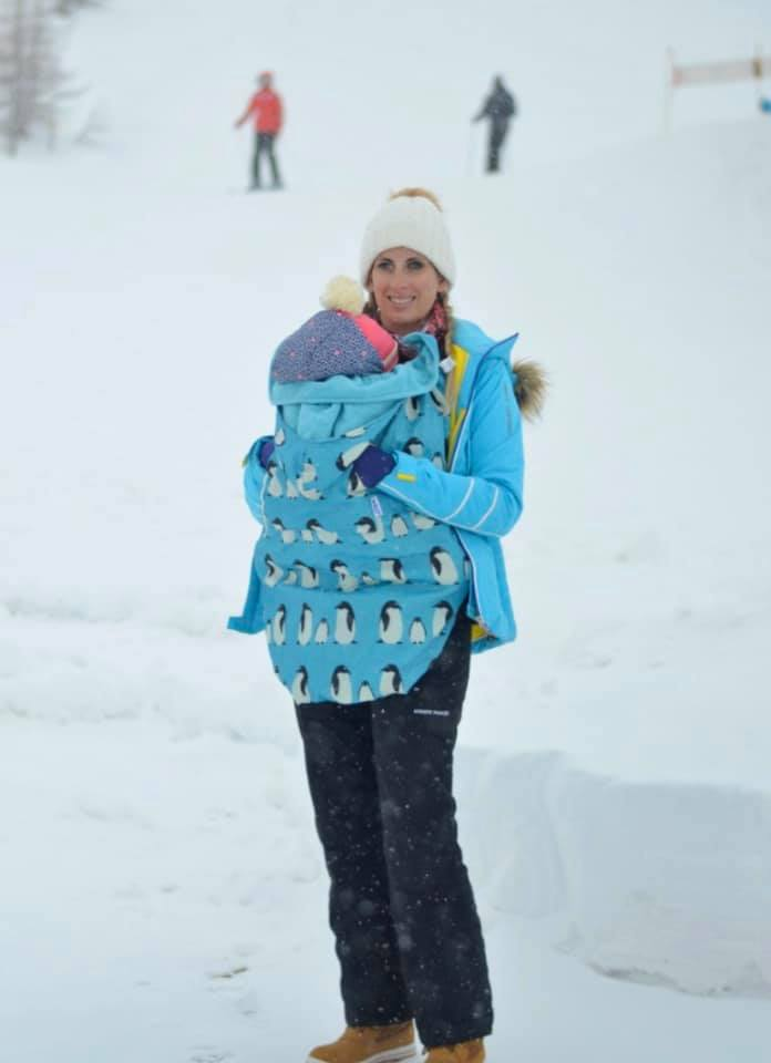 Mummy holding a baby in a snow sling whilst standing in snow