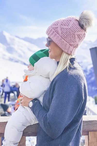 mummy holding a baby on the ski slopes looking out over mountains
