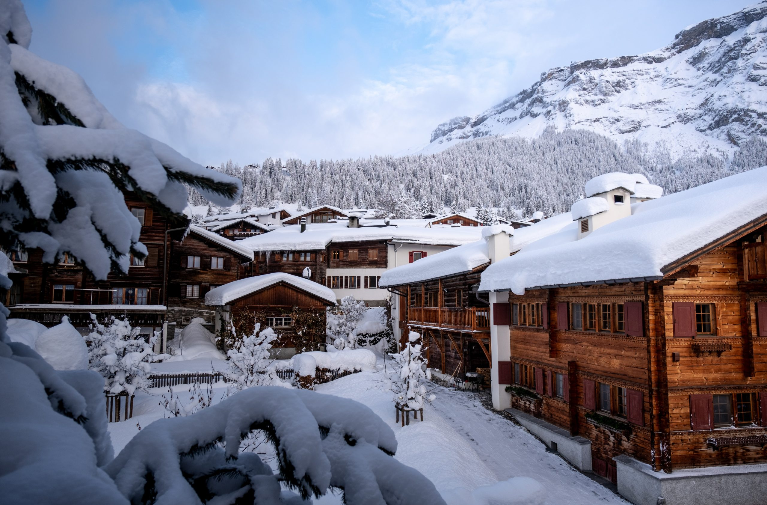 A row of wooden ski chalets covered in snow
