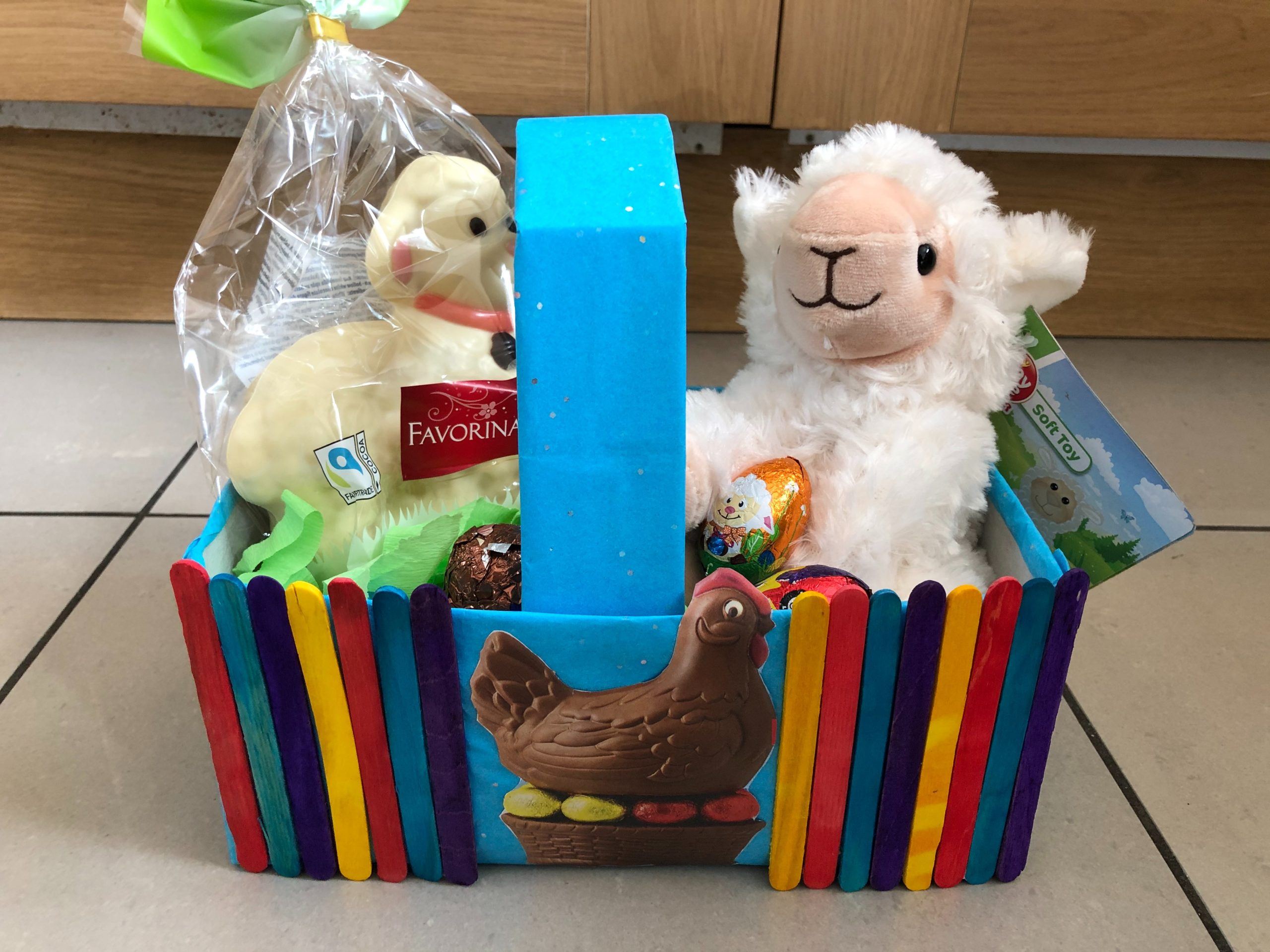 Multicoloured Easter basket made out of lollysticks. Inside the basket is a lamb and a duck