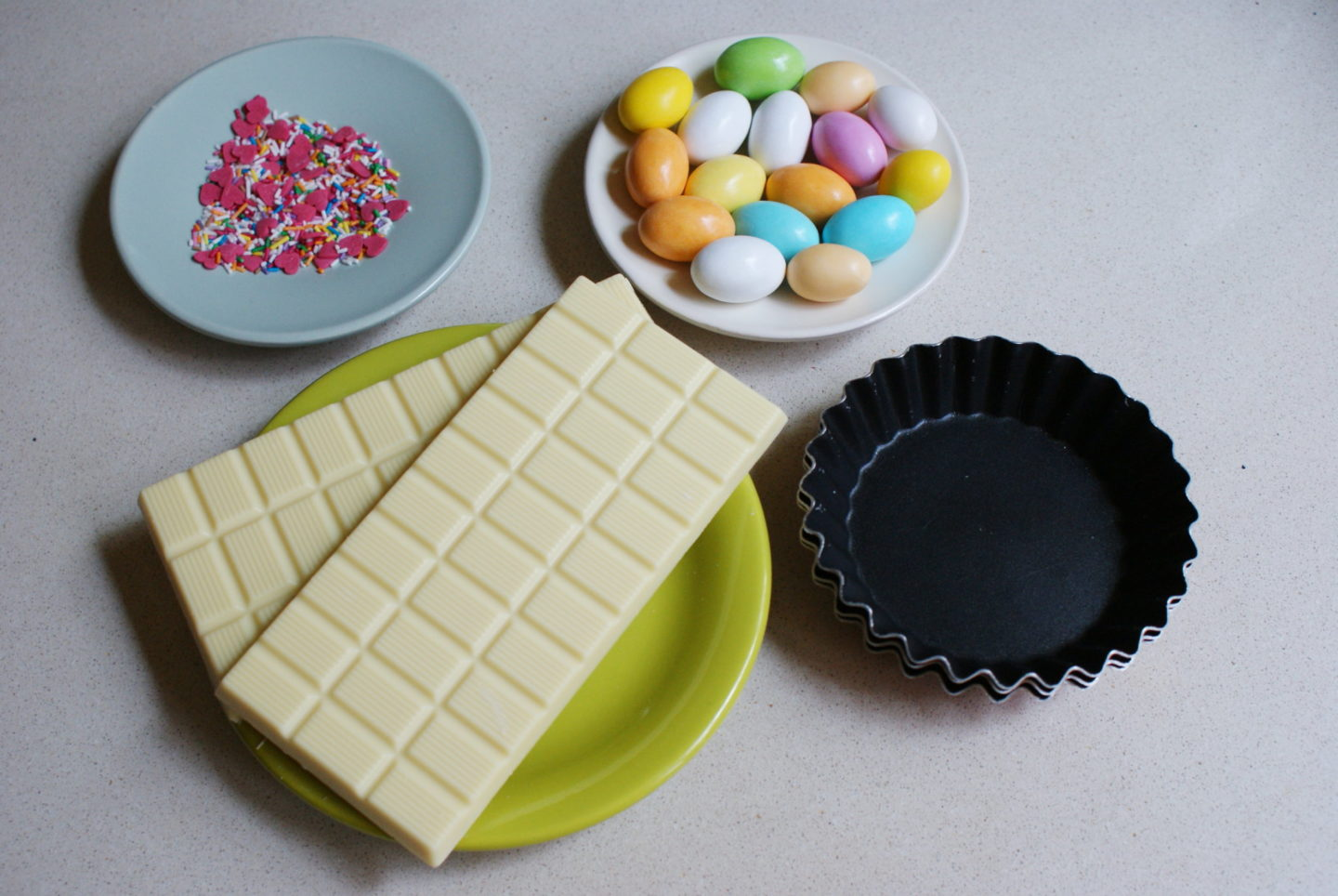 a tray with ingredients set out including multi coloured mini eggs, white chocolate, pink sprinkles and a cup case