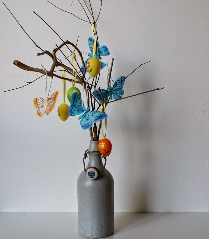 Easter table decoration made out of twigs which are in a grey vase. The branches have small decorations hanging from the branches.