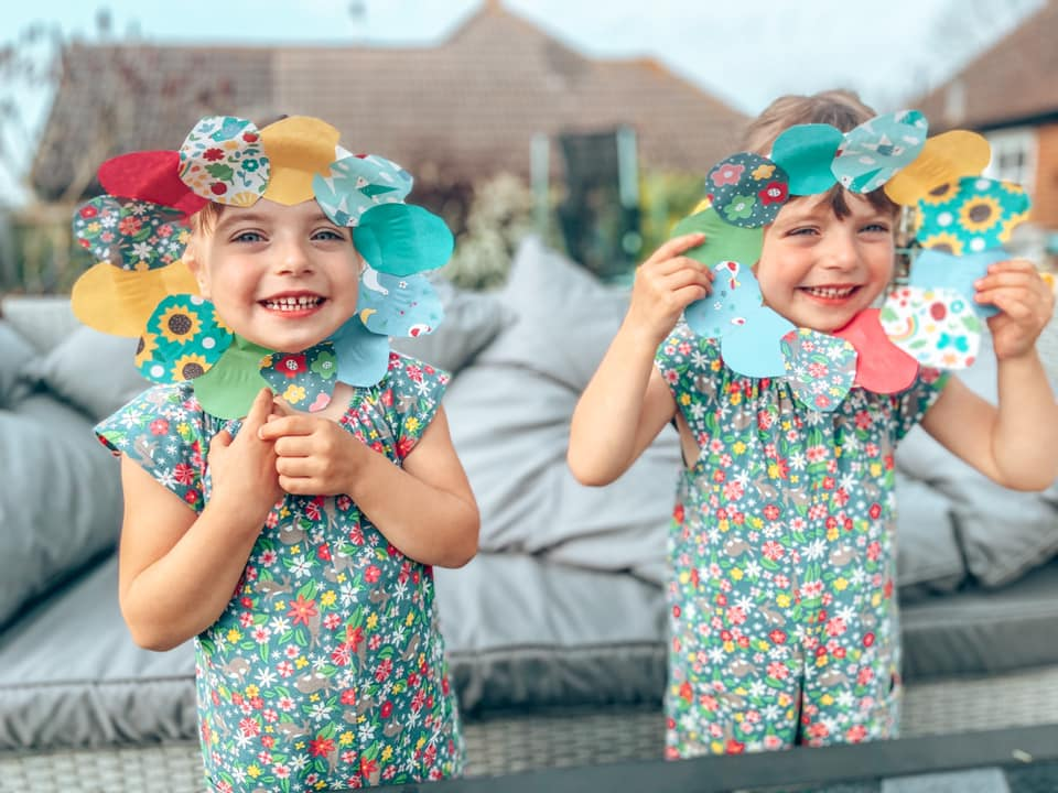 Easter Egg wreaths made from paper being held up to little girls faces