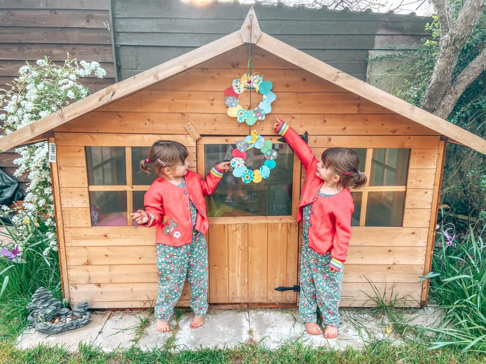 Twin girls standing outside a wooden playhouse in the garden. They are pointing at Easter Egg wreaths that they have just made