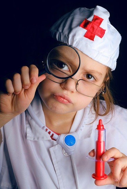 girl wearing glasses in a nurses outfit looking through a magnifying class holding a toy syringe