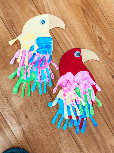Parrot craft using painted hand prints. Placed on the table completed. The hand prints on the cardboard parrot are multi coloured
