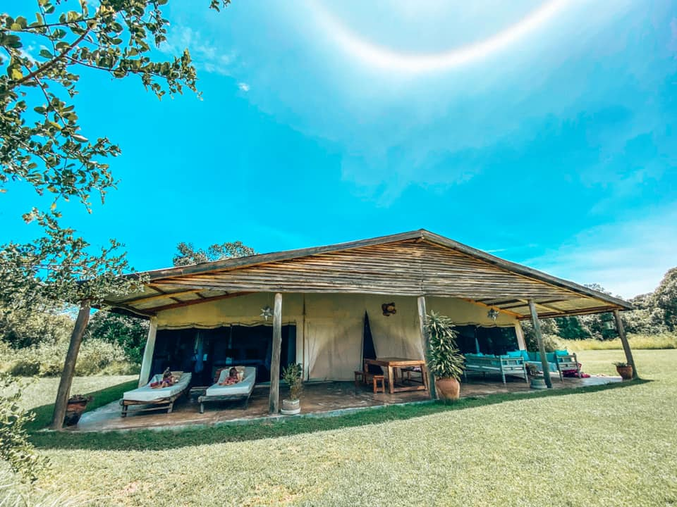 view of the Marula cottage from he outside with outdoor living space, loungers and lawn